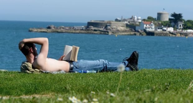 A man sunbathing on a green lawn while reading with the sea in the background