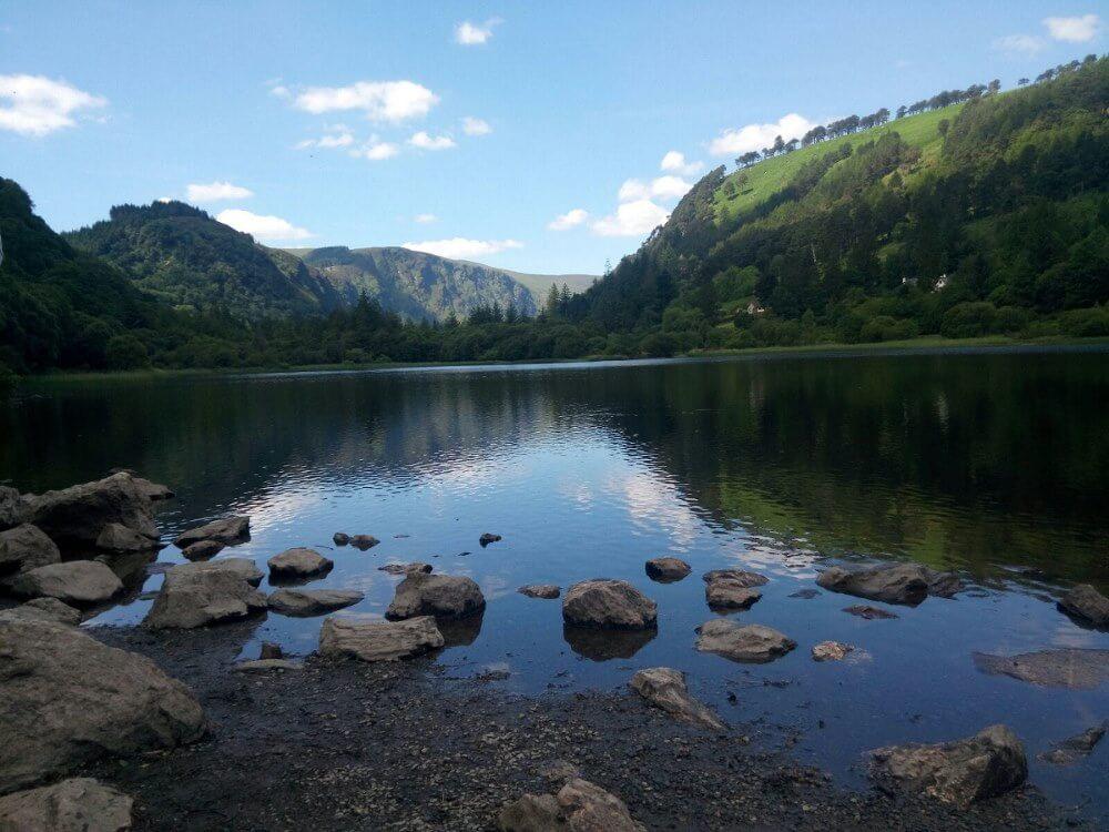 Lago pittoresco con montagne verdi sullo sfondo e un cielo blu