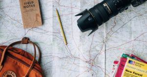 Backpack, camera and notes onto map