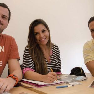 Three students smiling in class